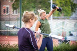 vrouwen trainen met dumbell en halter